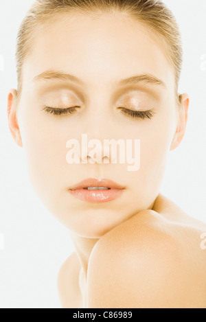 Woman with eyes closed, wearing natural cosmetics, resting chin on shoulder - Stock Photo