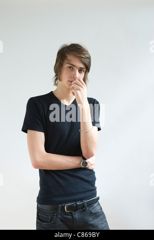 Young man looking pensively at camera, portrait - Stock Photo