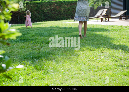 Mother and daughter walking in backyard - Stock Photo