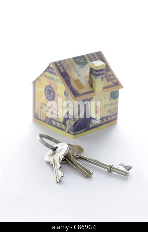 Bunch of keys and model house folded with dollar bills - Stock Photo