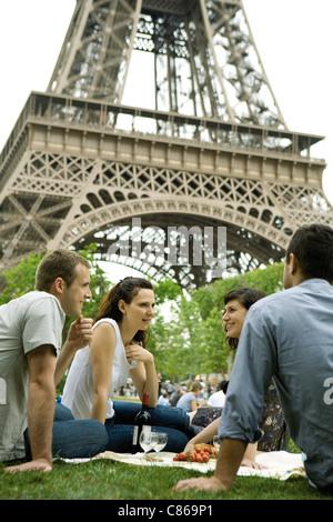 Tourists enjoying picnic at Eiffel Tower, Paris, France - Stock Photo