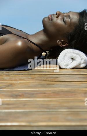 Woman sunbathing, lying on deck - Stock Photo