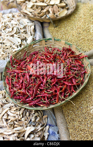 Red chillies and dried mango skins on sale at Khari Baoli spice and dried foods market, Old Delhi, India - Stock Photo