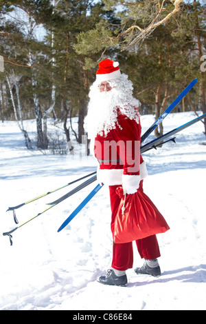 Portrait of Santa Claus with skis and sack of presents - Stock Photo