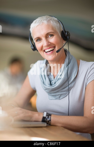 Older woman in headset using laptop - Stock Photo