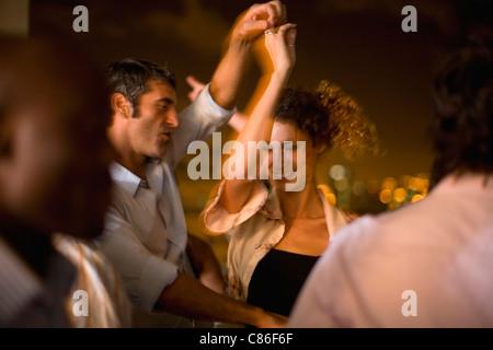 Couple dancing at party at night - Stock Photo