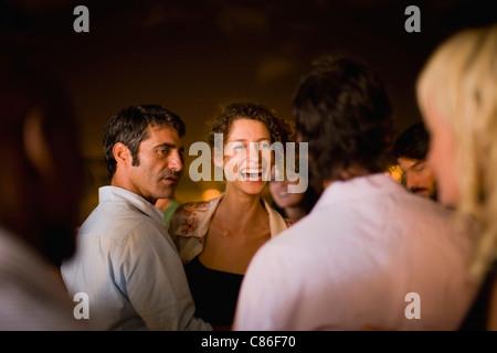 Woman laughing at party at night - Stock Photo