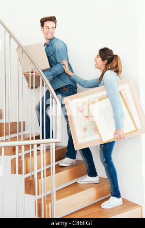 Couple moving boxes upstairs in new home - Stock Photo