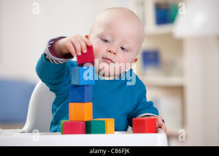 Baby boy playing with toy blocks - Stock Photo