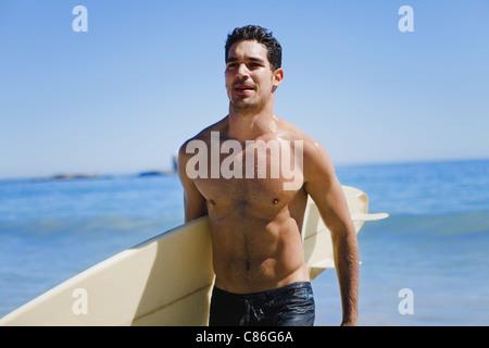 Man carrying surfboard on beach - Stock Photo