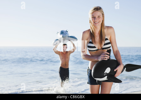 Couple playing with toys on beach - Stock Photo