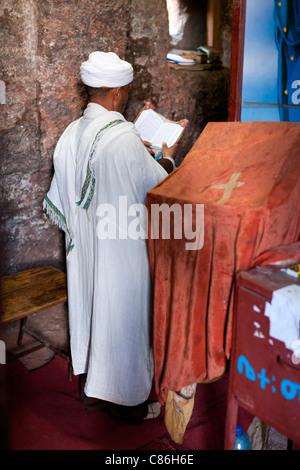 An Orthodox Christian priest praying inside the rock-hewn church of Bet Meskel in Lalibela, Northern Ethiopia, Africa. - Stock Photo