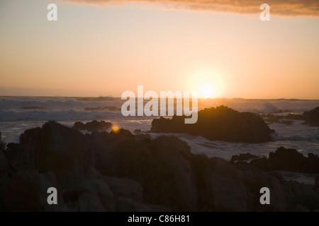 Waves crashing over rocks on beach - Stock Photo