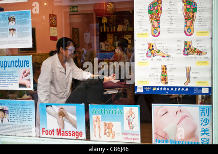 Man receiving back massage in Chinese medicine shop in Chinatown, Soho, London, United Kingdom - Stock Photo