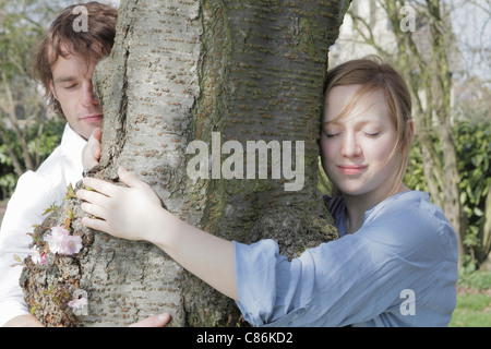 Couple hugging tree in park - Stock Photo