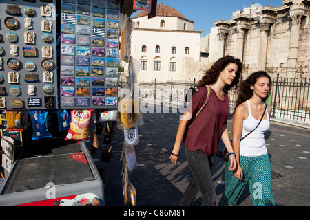 Women walking past a stall selling postcards and souvenirs to tourists in the area of Monastiraki, Athens, Greece. - Stock Photo