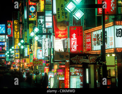 Neon lights and shops along walking street in Ginza district at night in Tokyo - Stock Photo