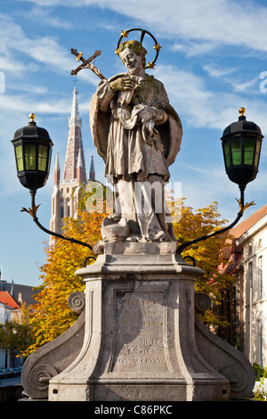 Statue of St.John of Nepomuk, Sint-Jan Nepomucenus, on Wollestraat Bridge in Bruges. Tower of Church of Our Lady - Stock Photo
