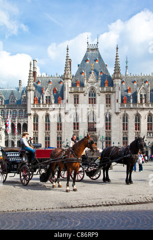 Tourist horse and carriage before the Provincial Court, Provincaal Hof in Grote Markt or Market Square, Bruges (Brugge), - Stock Photo