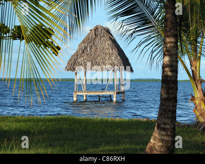 Tropical hut over water with thatched palm roof, Caribbean sea, Central America, Panama - Stock Photo