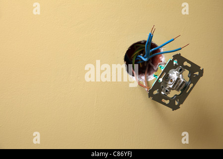 electrician installing a power socket wall background, Dirty socket hanging out of the wall - Stock Photo
