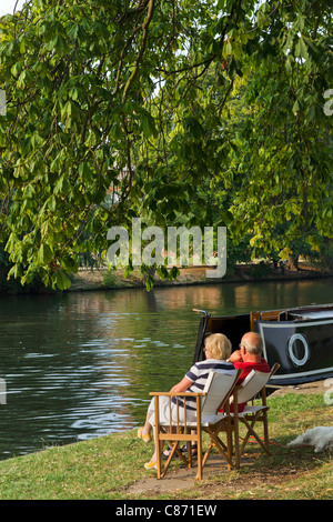 Couple sitting by their narrowboat on banks of River Avon in late afternoon sun, Stratford-upon-Avon, Warwickshire, - Stock Photo