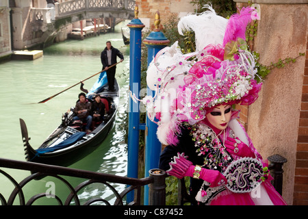Gondola and masquerader in mask, the Venice Carnival, Venice, Italy - Stock Photo