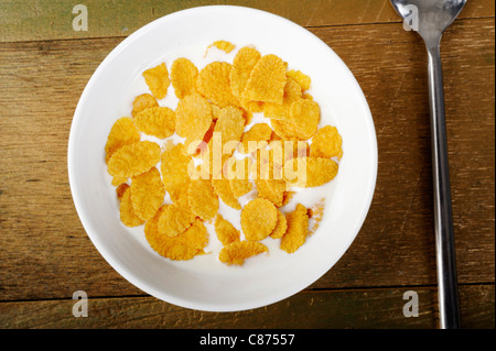 Cornflakes and milk in bowl - Stock Photo
