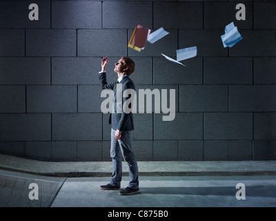 young business man walking out from office parking and throwing away paperworks. Horizontal shape, side view, copy - Stock Photo