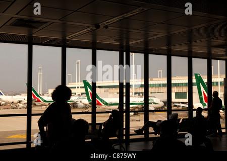 Rome Fiumicino Leonardo da Vinci airport terminal 2 interior silhouetted people and view of runway Passengers waiting - Stock Photo