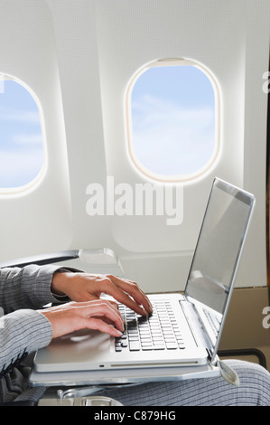 Germany, Bavaria, Munich, Close up of businesswoman's hand using laptop in business class airplane cabin - Stock Photo