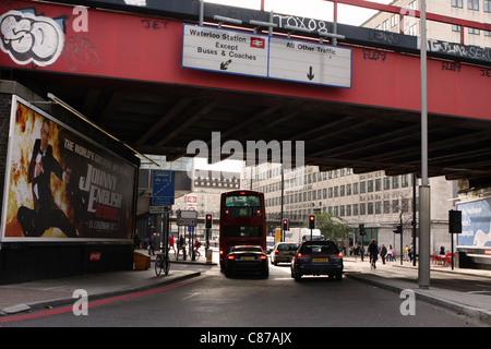 a bus and cars waiting under a bridge for traffic lights to change from red to green - Stock Photo