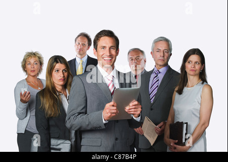 Business people with digital tablet, file, diary, mobile phone and newspaper against white background - Stock Photo