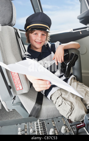 Germany, Bavaria, Munich, Boy wearing captain's hat and holding paper plane in airplane cockpit - Stock Photo