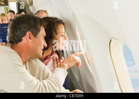 Germany, Munich, Bavaria, Man and women looking out through window in economy class airliner - Stock Photo