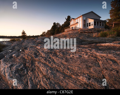 Sunset scenery of a cottage house on a beautiful rocky shore - Stock Photo