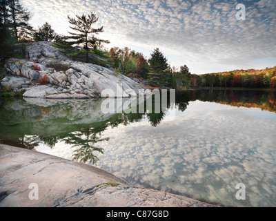 Rocks and autumn trees on a shore of lake George. Beautiful fall nature scenery. Killarney Provincial Park, Ontario, - Stock Photo