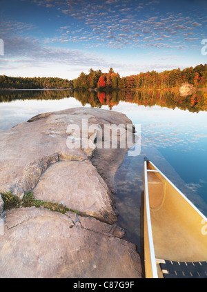 Canoe at a rocky shore of lake George. Beautiful sunset fall nature scenery. Killarney Provincial Park, Ontario, - Stock Photo