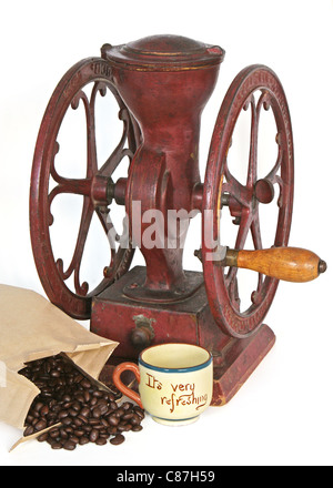 Antique red coffee grinder with whole beans and empty cup. - Stock Photo