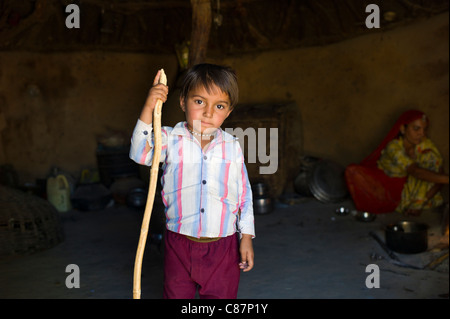 Indian boy in home made of mud bricks and cow dung in Bishnoi tribe village near Rohet in Rajasthan, India - Stock Photo