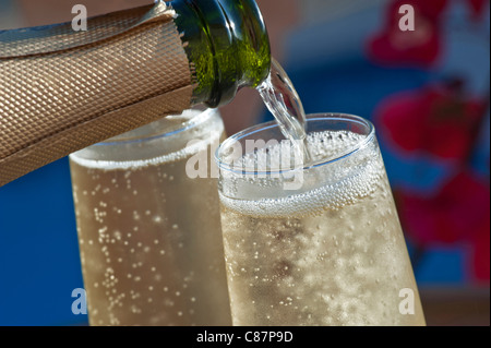 Champagne sparkling wine pouring alfresco closeup chilled glasses of wine on sunny terrace with Bougainvillea flowers - Stock Photo