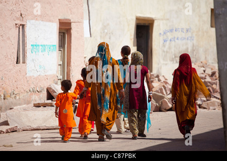 Indian women and girls dressed as wedding guests walking to the wedding in village of Rohet in Rajasthan, Northern - Stock Photo