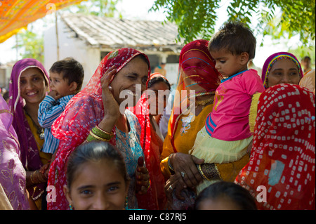 Indian wedding with guests dressed in their finest embellished saris in village of Rohet in Rajasthan, Northern - Stock Photo