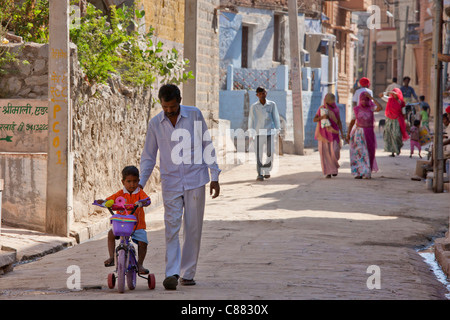 Indian man with child on tricycle in the village of Narlai in Rajasthan, Northern India - Stock Photo