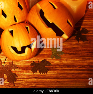 Halloween pumpkins holiday border, autumn wooden background, traditional jack-o-lantern over wood with dry leaves, - Stock Photo