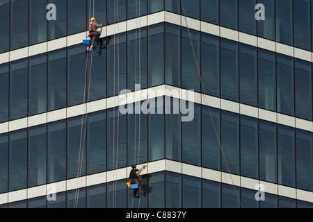 Absiling window cleaners work high above street level of the glass sheets of Westfield City shopping centre in Stratford. - Stock Photo