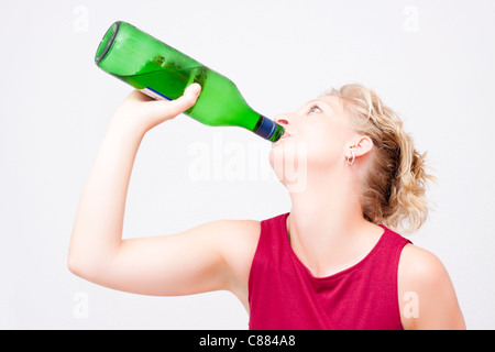 Young woman with bottle of alcohol. - Stock Photo