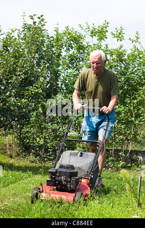 Portrait of elderly man mowing lawn in the garden. - Stock Photo