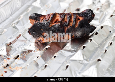 Detail of totally burnt sausage on tinfoil. - Stock Photo