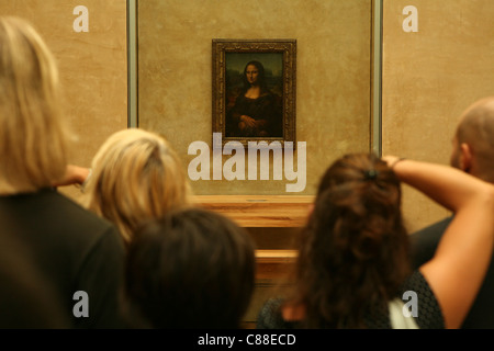 Visitors taking pictures of Mona Lisa by Leonardo da Vinci in the Louvre Museum in Paris, France. - Stock Photo